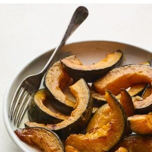 Plate with cinnamon maple roasted kabocha squash. Serving fork is on the bowl as well.