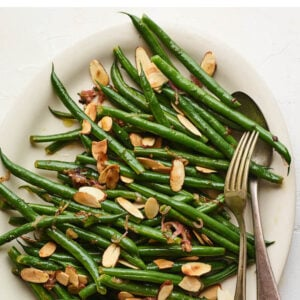 An overhead photo of a serving dish holding green beans almondine. A serving fork and spoon lay on the side of the dish.