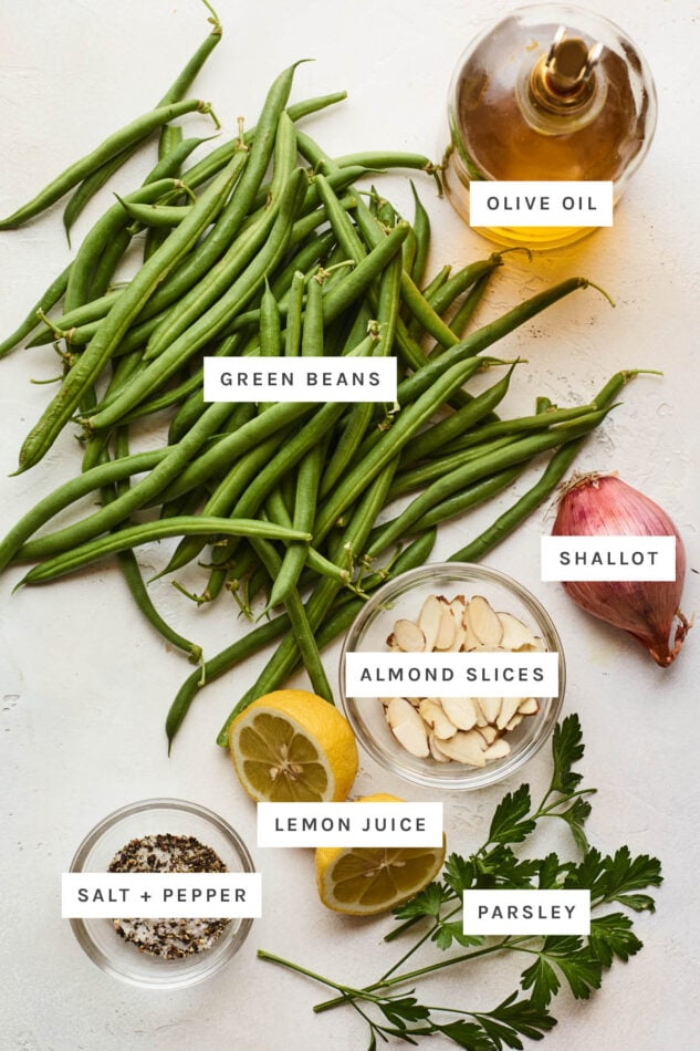 Ingredients measured out to make green beans almondine: olive oil, green beans, shallot, almond slices, lemon juice, salt, pepper and parsley.