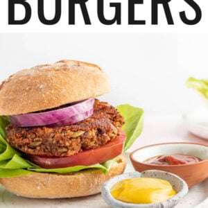 A black bean pumpkin burger on a bun with lettuce, tomato and onion. The burger is on a plate with two small ramekins of mustard and ketchup.