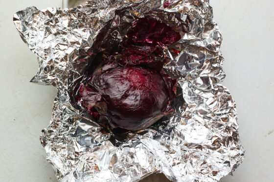 A beet freshly roasted in tin foil.