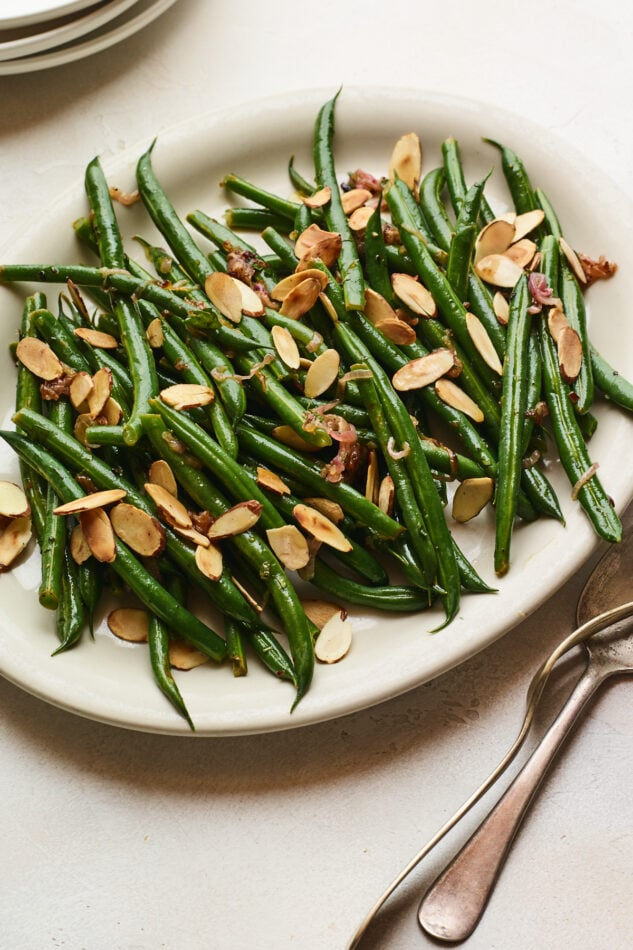 An closeup overhead photo of a serving dish holding green beans almondine. A serving fork and spoon lay next to the dish.
