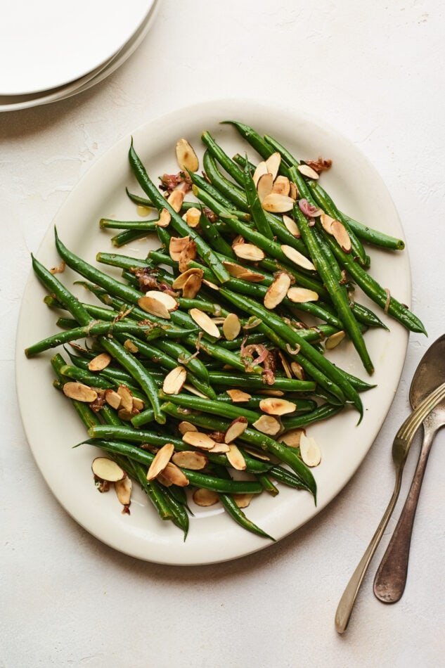 An overhead photo of a serving dish holding green beans almondine. A serving fork and spoon lay next to the dish.