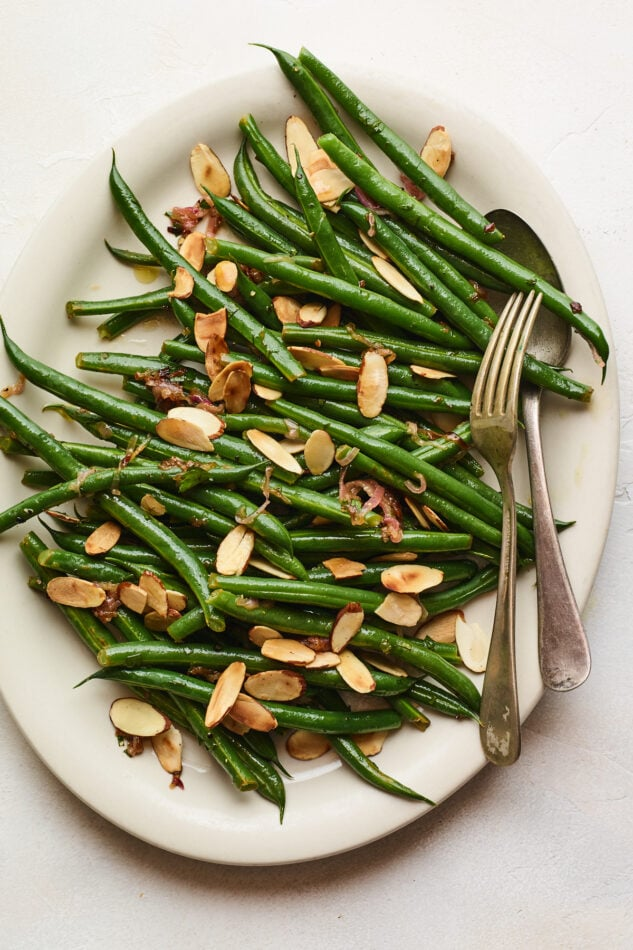 An overhead photo of a serving dish holding green beans almondine. A serving fork and spoon lay across the green beans..