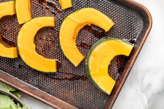 Slices of kabocha squash on a baking pan drizzled with oil.