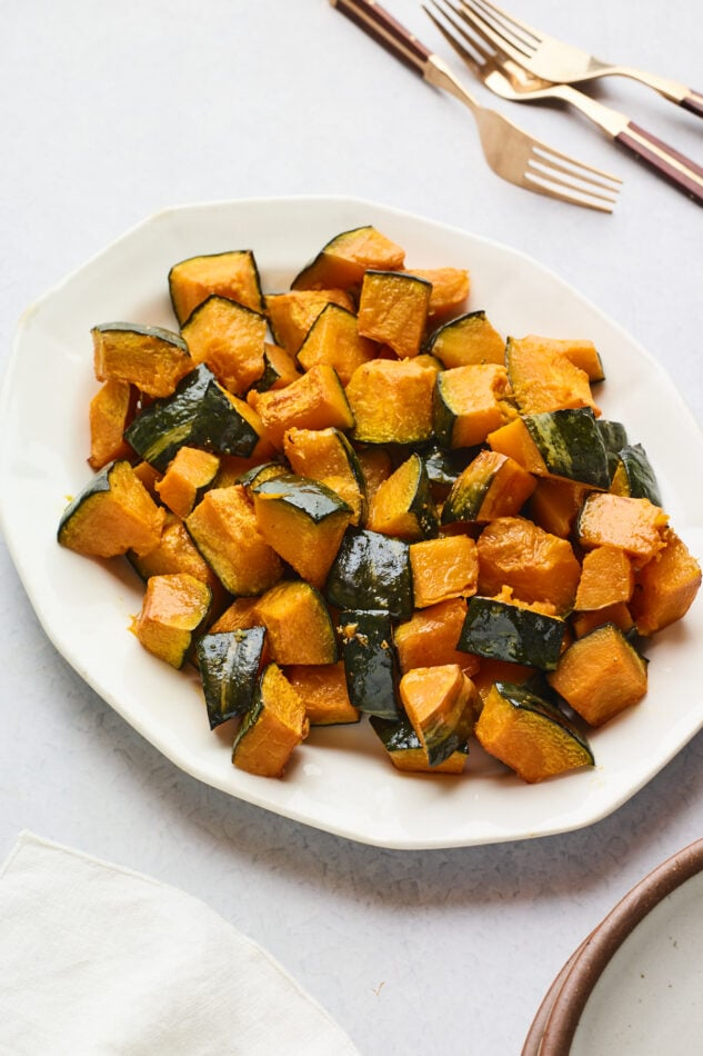 A serving dish full of roasted Kabocha tots. A few forks lay at the top of the frame.