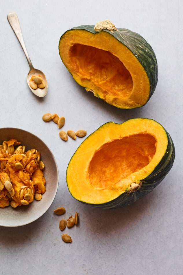 A Kabocha squash cut in half with the seeds removed and in a bowl.