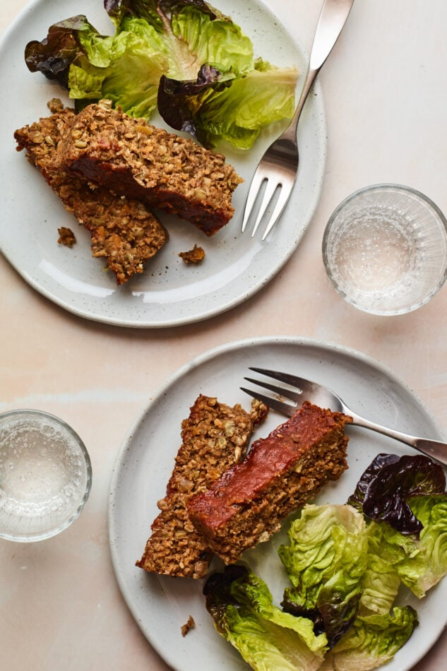 Two plates with two slices of lentil loaf and salad greens. Additionally, there are two forks and two glasses of water.