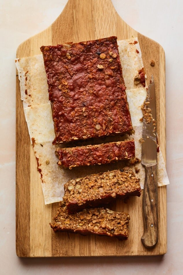 An overhead shot of a cutting board with a partially sliced lentil loaf on parchment paper. A knife lays on the cutting board perpendicular to the loaf.