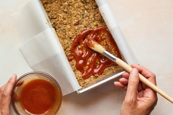 Lentil loaf mixture in a bread pan being coated with maple sweetened glaze by a hand using a small brush.
