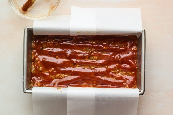 Lentil loaf coated with maple sweetened glaze in a bread pan lined with parchment paper, ready to be baked.