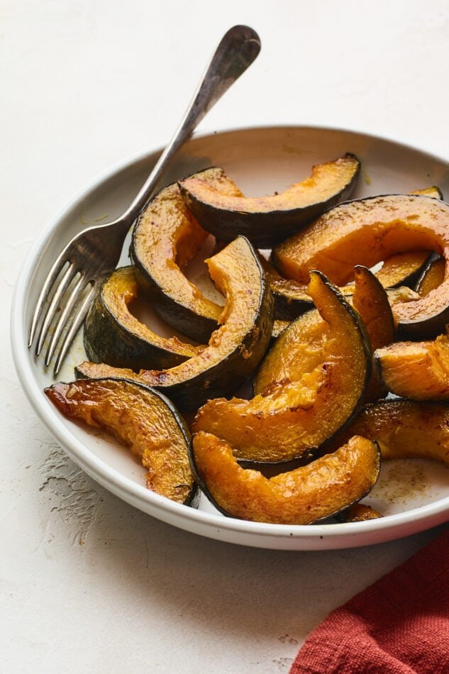 A shallow bowl with slices of cinnamon maple roasted Kabocha squash. A fork rests inside the bowl.