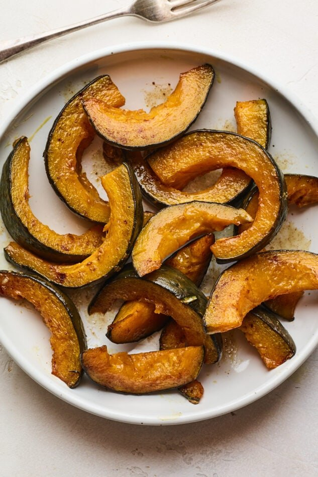 An overhead photo of a plate of cinnamon roasted Kabocha squash slices. A fork rests next to the plate.