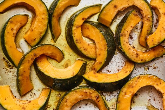 Slices of Kabocha squash covered in oil and seasoning on a sheet pan, ready to be roasted.