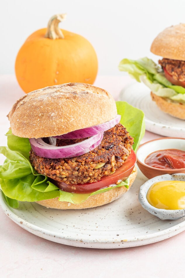 A black bean pumpkin burger on a bun with lettuce, tomato and onion. The burger is on a plate with two small ramekins of mustard and ketchup. There is a small pumpkin in the background.